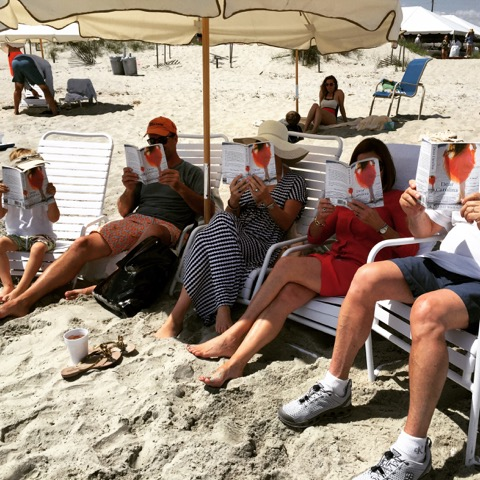Family Reading Her First Book on the Beach