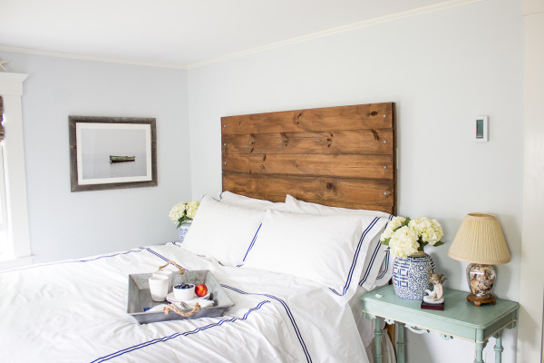 Crisp white bedding against a rustic headboard make for a welcoming spot.