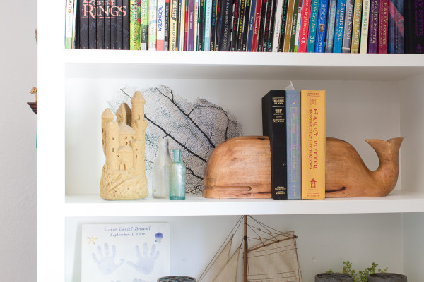 Bookshelf with beautiful whale book ends.