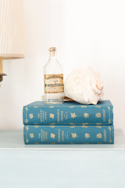 Pretty shell with antique books and bottle add the right touch to a painted desk.