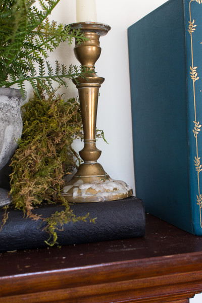 Brass candlesticks with dripping wax adds a romantic feeling to a moss covered mantel I www.findingsilverpennies.com