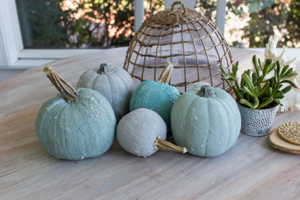 A wash table set with saltwash pumpkins and some greenery.