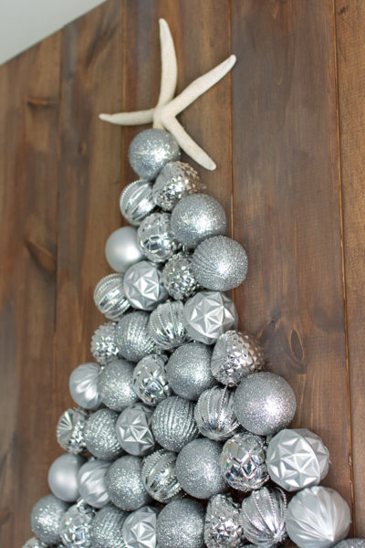 Pretty ornaments create a festive tree with a starfish topper.