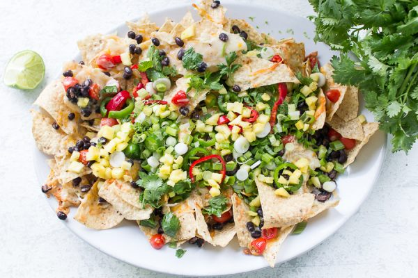 Mouth watering three cheese nachos loaded with fresh veggies and cilantro
