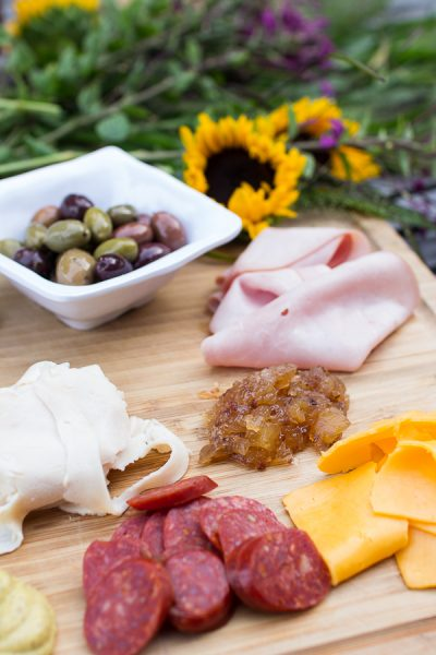 mouth watering chefs board with olives, artisan cheese and delicious meats