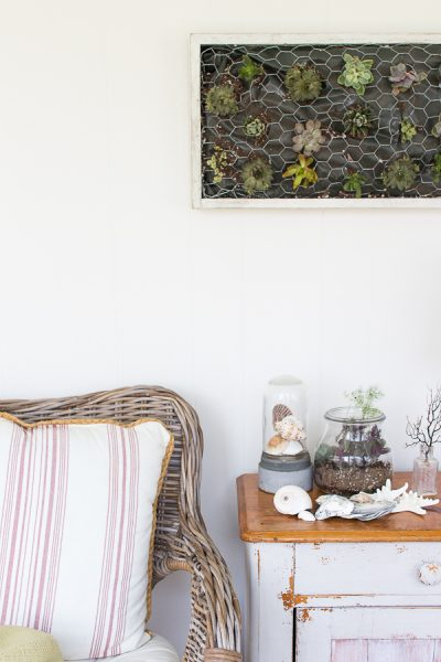 A coastal sunroom with a pretty succulent wall hanging