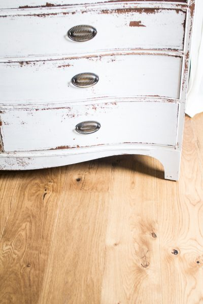 chippy white dresser and rustic wood floors