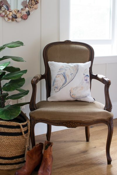 A vintage chair with a watercolor oyster pillow