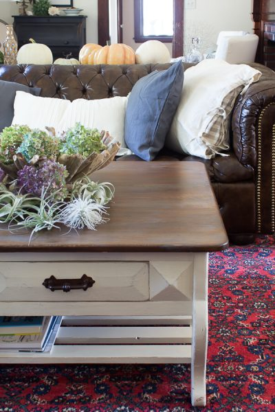 A Rustic Table with Dried Hydrangeas and a tufted leather couch with linen pillows is perfect for fall