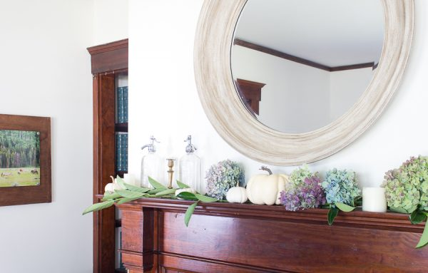 Soft greenery lines a mantel with an oversized weathered mirror