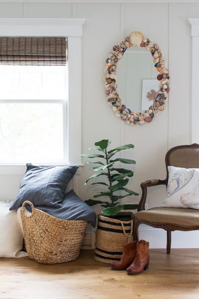 Simple Coastal Style - warm woods, woven blinds, board and batten walls, and shells make this room lovely.