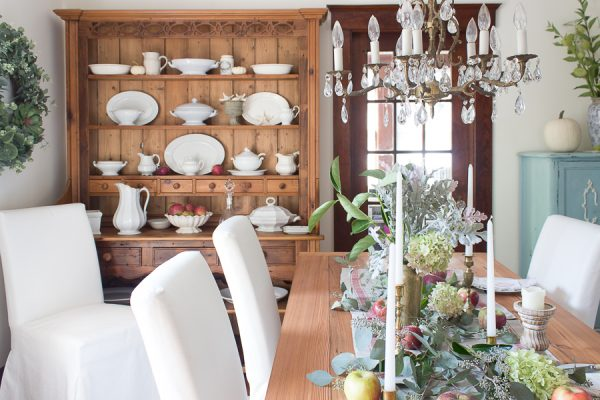 White slipcovered chairs, a welsh dresser and pine table - pretty rustic dining room