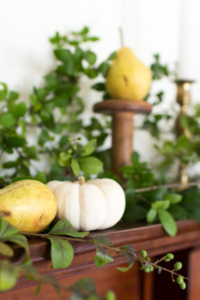 Using natural elements to create a gorgeous mantel- pears, white pumpkins, privet, and brass candlesticks