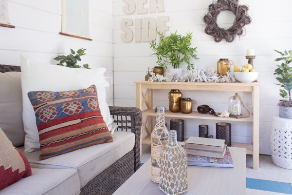 Layers of fall texture - kilim pillows, rattan bottles, copper lanterns and woven seating