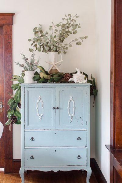 Blue milk painted cabinet with eucalyptus and magnolia leaves I Finding Silver Pennies