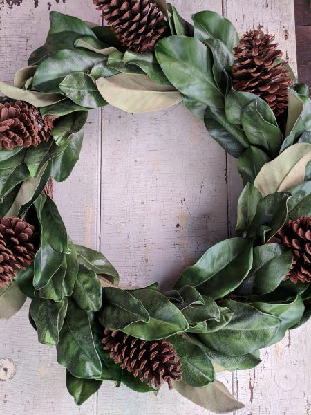 Simple wreath of magnolia leaves and pinecones on a chippy door I Finding Silver Pennies