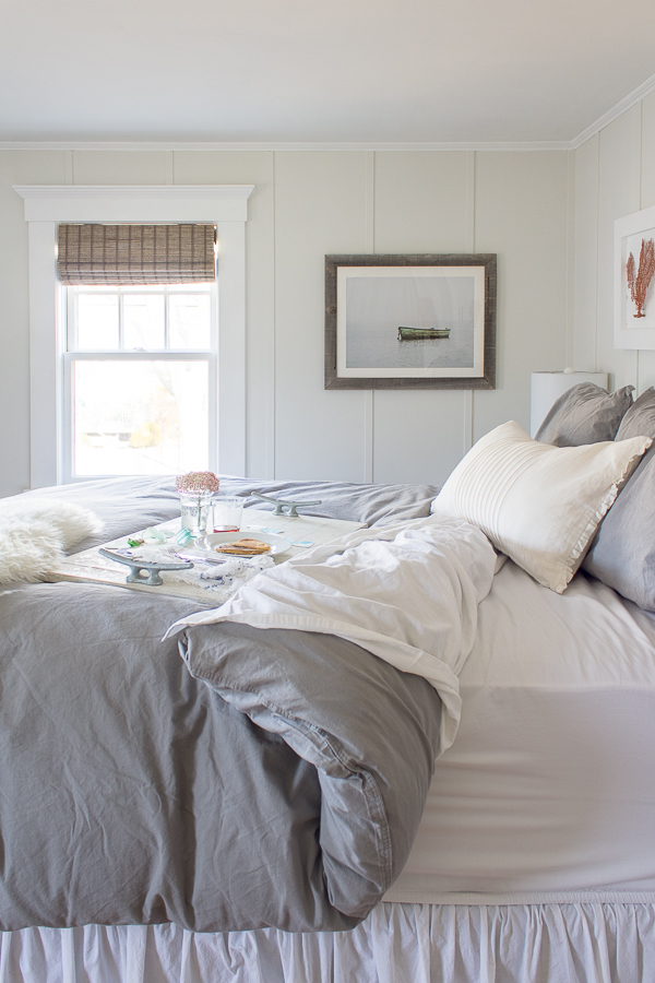 Cozy and Coastal. A pretty bedroom to curl up in with gray bedding, woven shades and board & batten paneling I Finding Silver Pennies