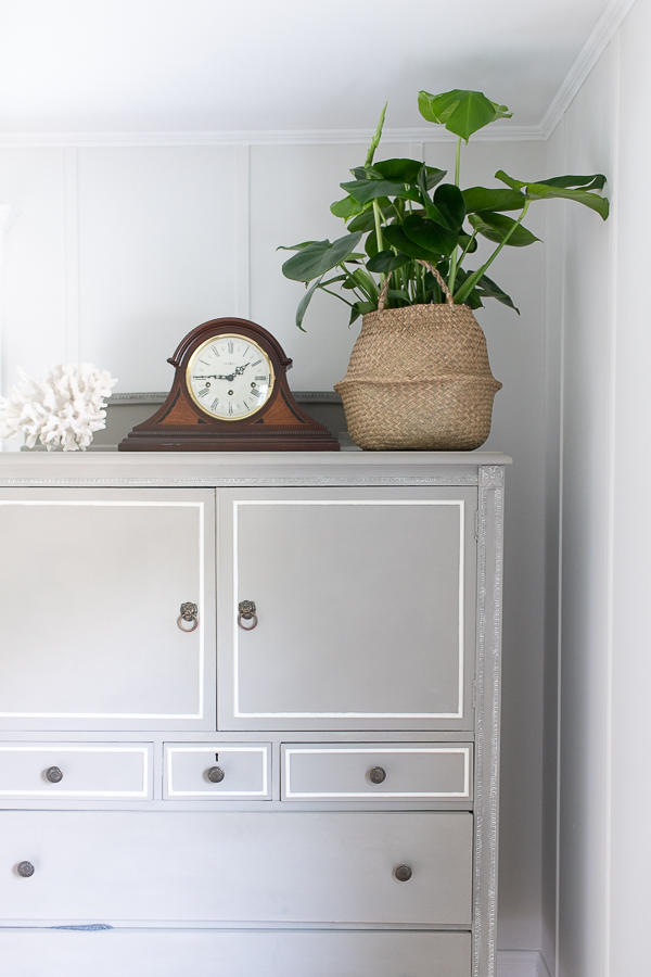 Painted armoire with a pretty monstera plant in a basket, coral and an antique clock - Finding Silver Pennies