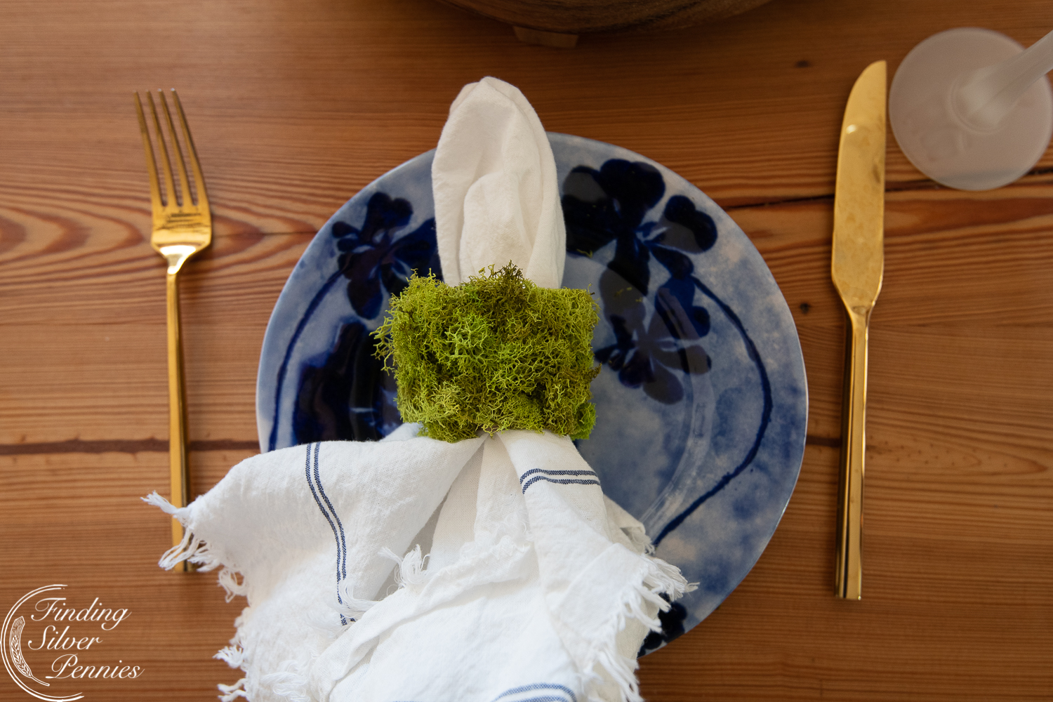Simple table setting with gold silverware and moss napkin holders