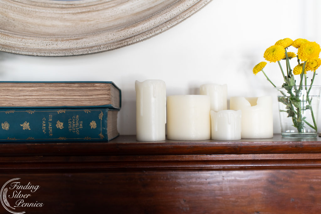 drippy candles, worn books, and yellow flowers #spring #mantel #flowers #seasonalsimplicity