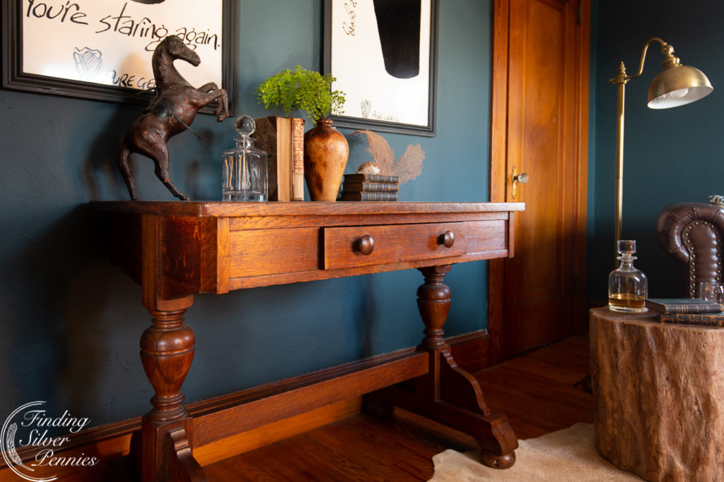A vintage Stickley library table grounds a moody home office.