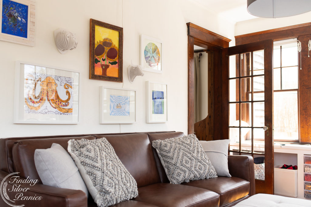 Kids art above a modern leather couch   Finding Silver Pennies